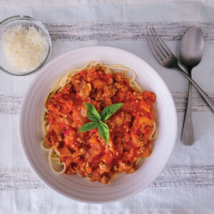Pasta with pumpkin sauce and sausage on it