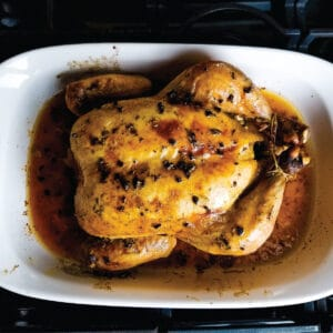 Whole chicken in the roasting pan resting after being baked