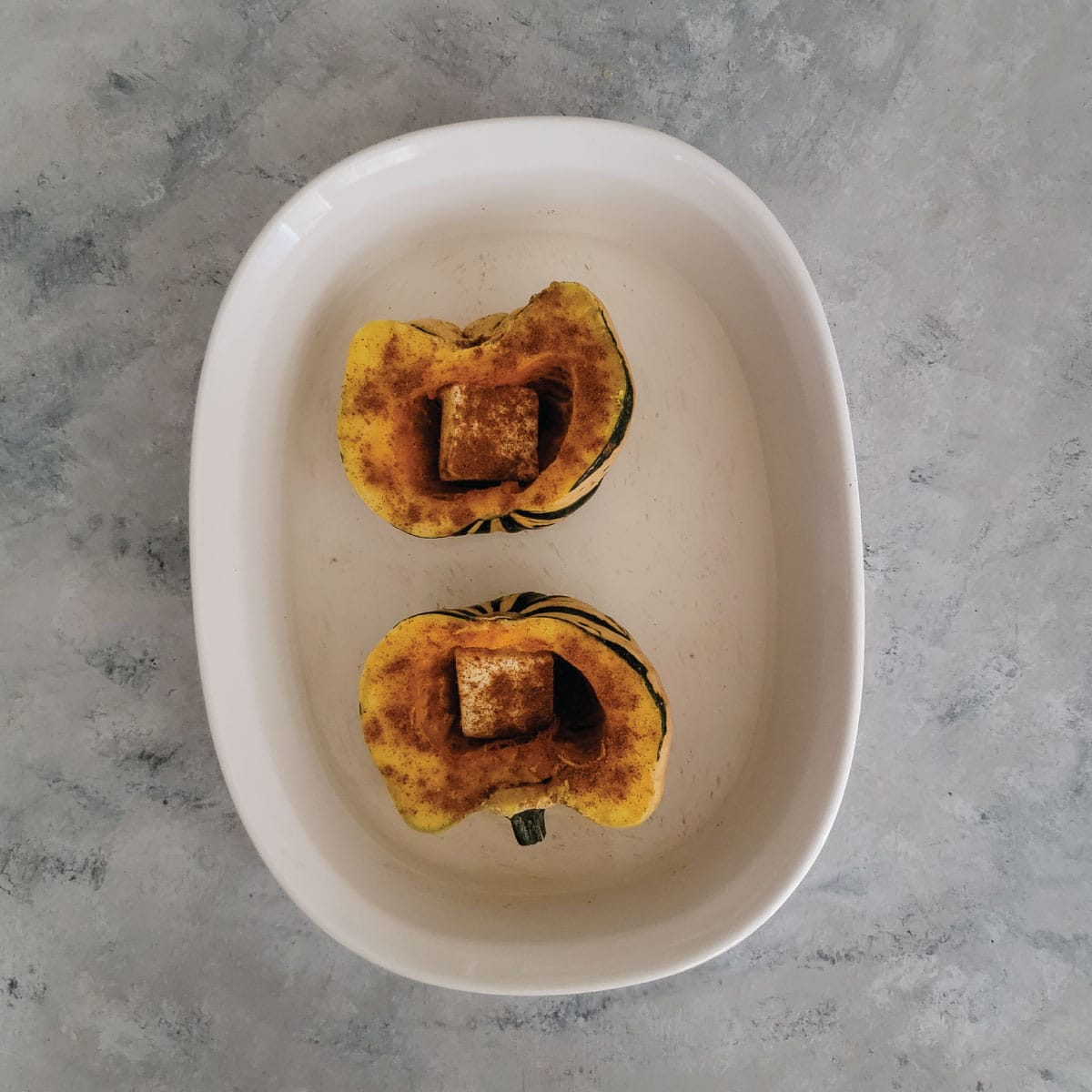 Squash cut in half in a baking dish with a slice of butter in the cavity where the seeds were and spices sprinkled on all over the top.