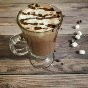 Hot chocolate in a cup with marshmallow froth and drizzled chocolate