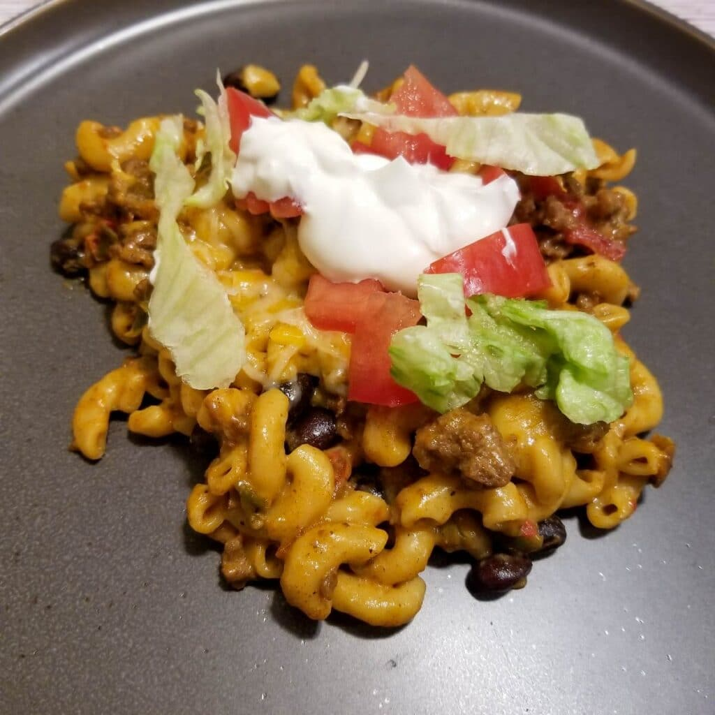 Taco pasta on a plate with sour cream, lettuce and tomato