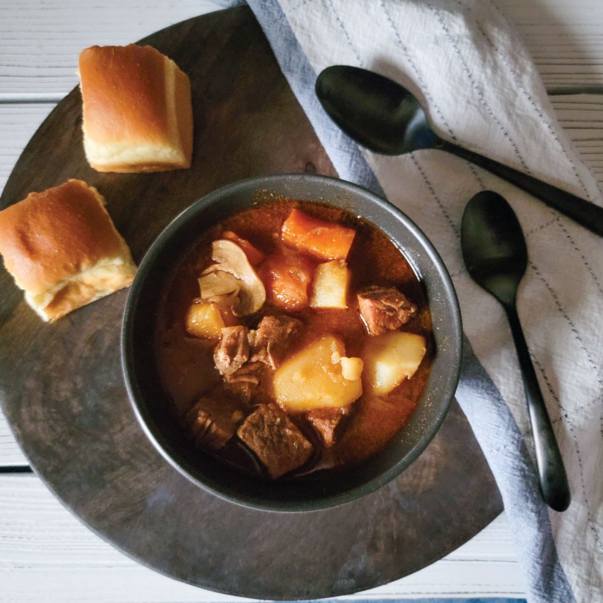 beef stew in a bowl ready to be served with 2 dinner rolls