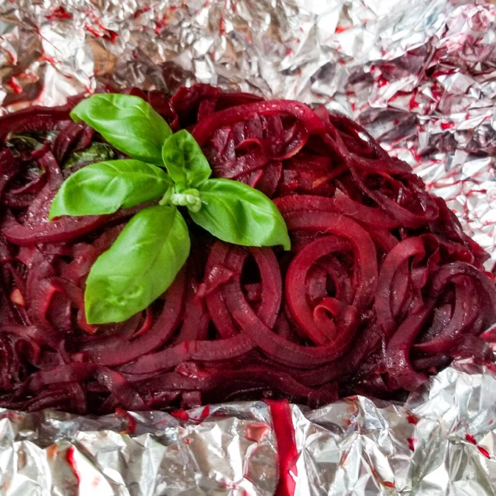 Cooked spiralized beets in the open foil packet with basil on top as a garnish