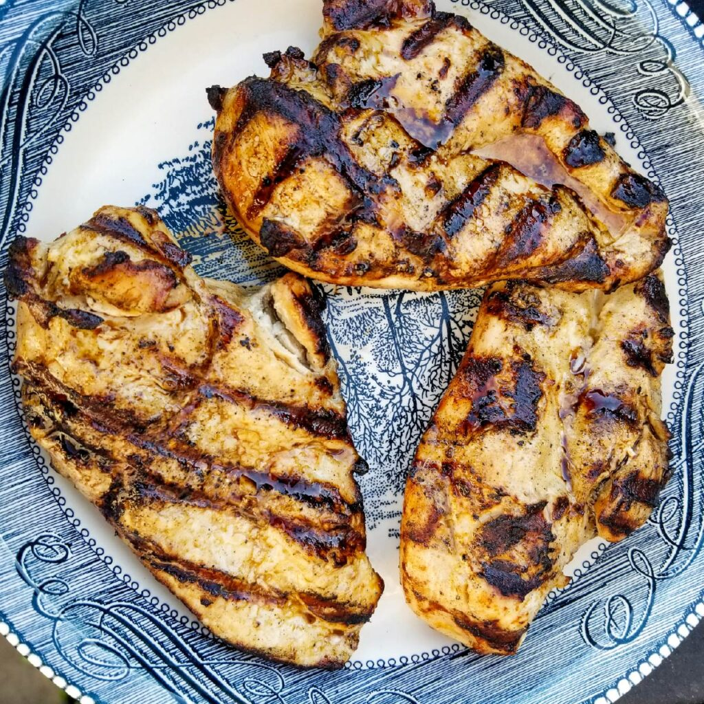 grilled chicken breasts on a plate resting after coming off the grill