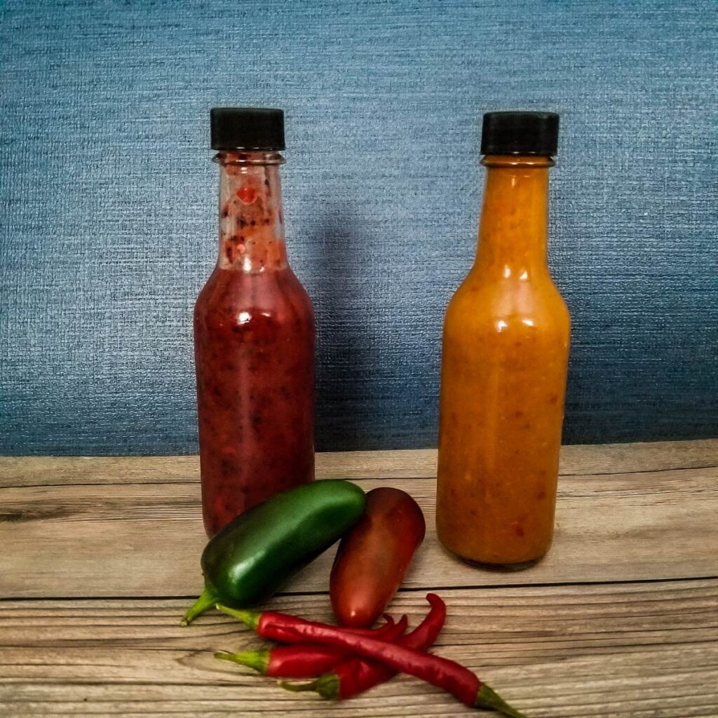 bottled hot sauce in 5 ounce bottles with hot peppers next to them
