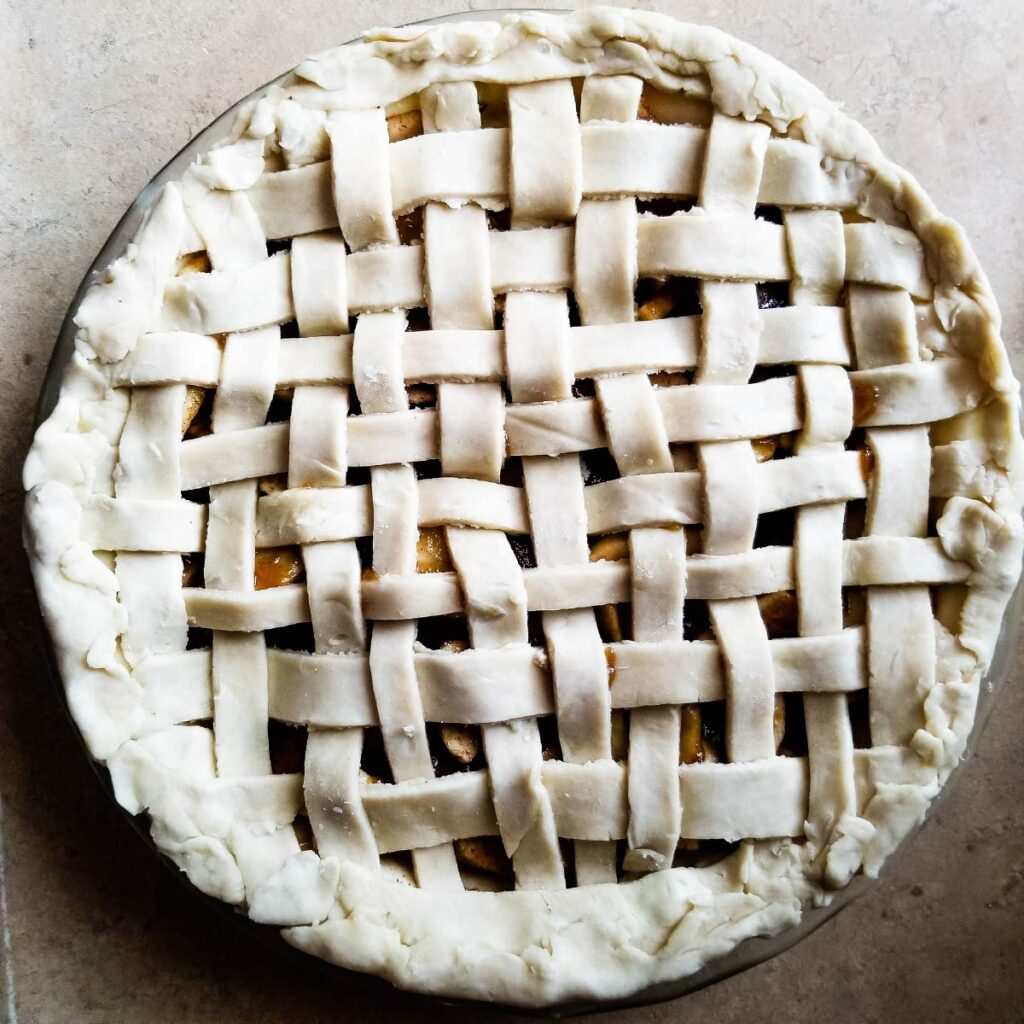 Lattice crust on top of the pie that is ready to go in the oven.
