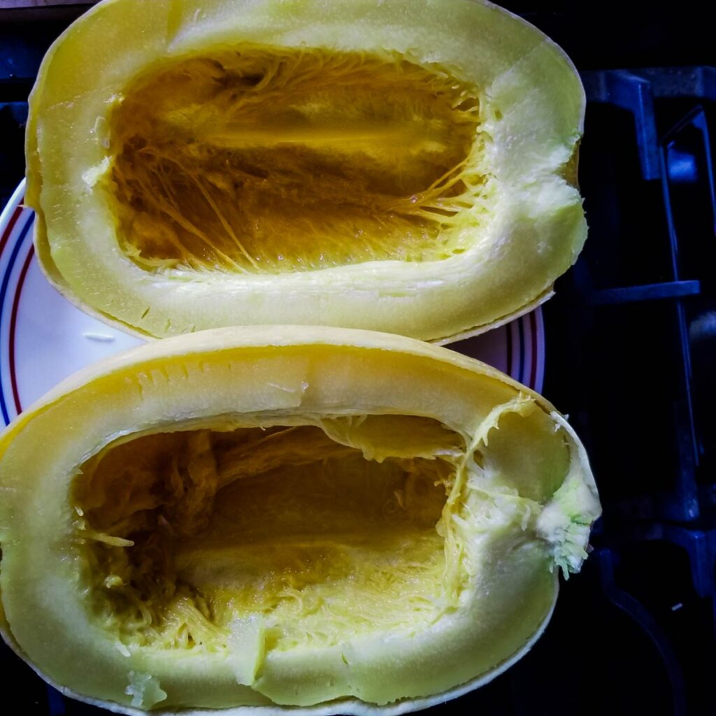 Spaghetti squash cut in half on a plate after being cooked