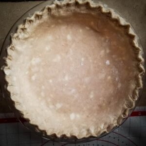 pumpkin pie crust shaped into pie dish ready for filling