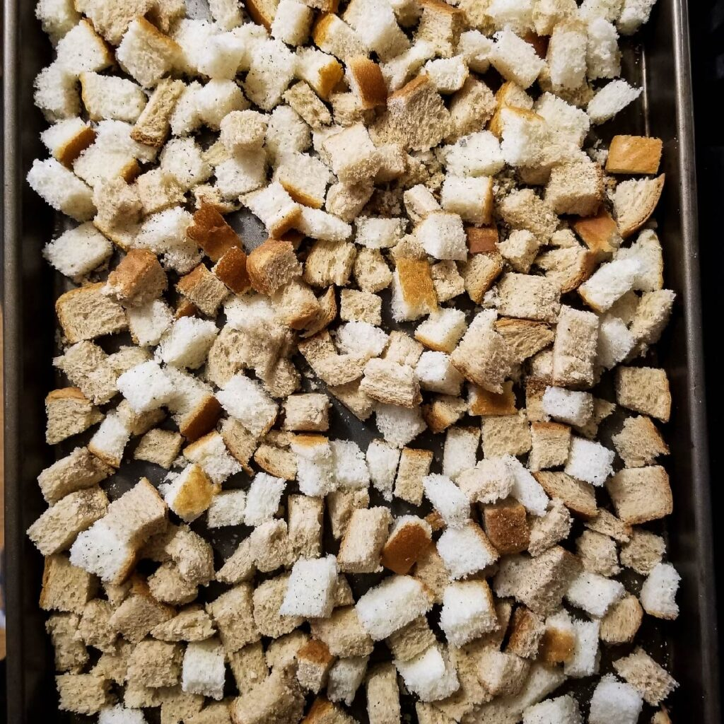 Bread cubes on a baking tray that just came out of the oven.