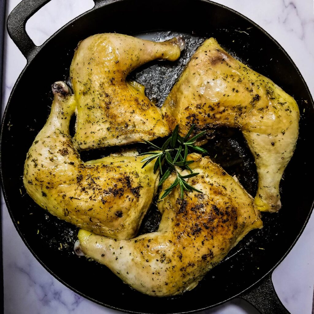 Chicken leg quarters in a pan after cooking ready to be served