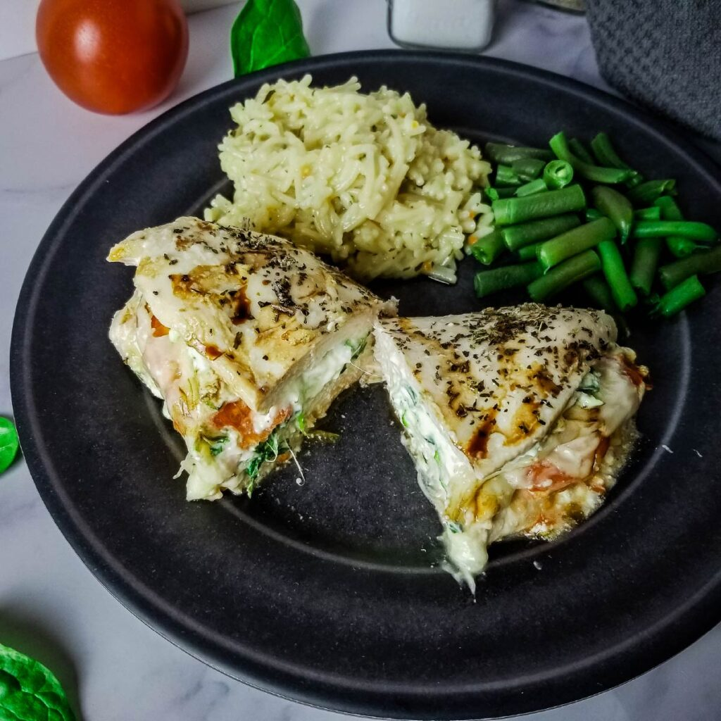 Stuffed chicken breast on a plate cut in half with rice and green beans.