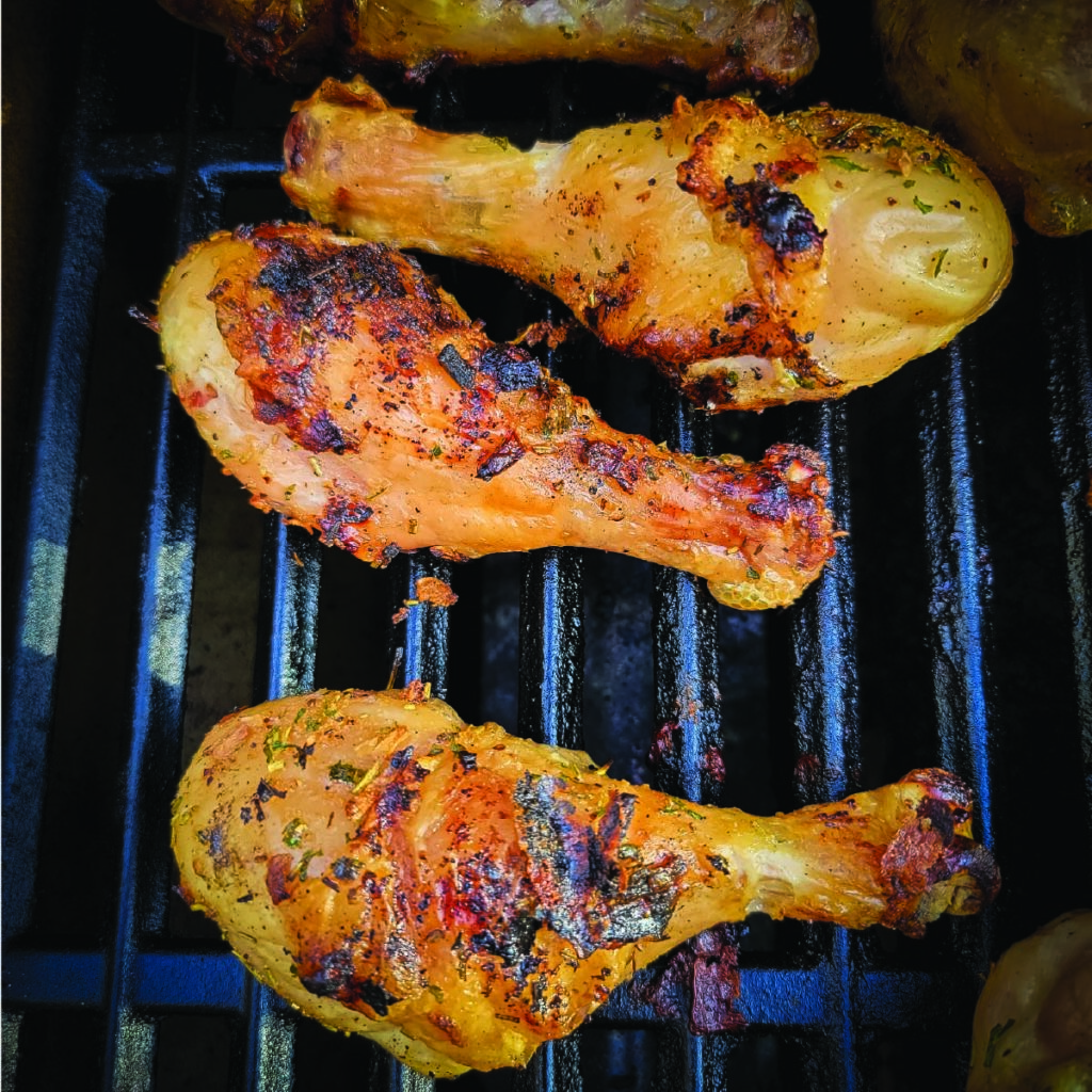 chicken legs on the grill with a crispy skin just before coming off to serve