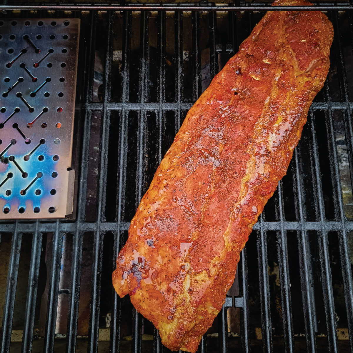 Ribs on a grill cooking with a smoke box next to them
