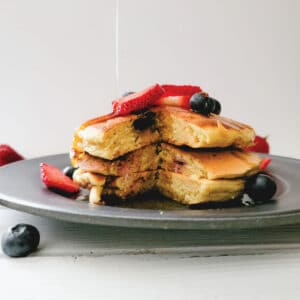 Pancakes on a plate topped with blueberries and strawberries while maple syrup is being poured over them