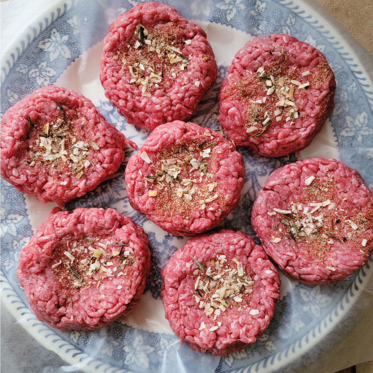 beef shaped into burgers with spices on top sitting on a plate ready to put on the grill