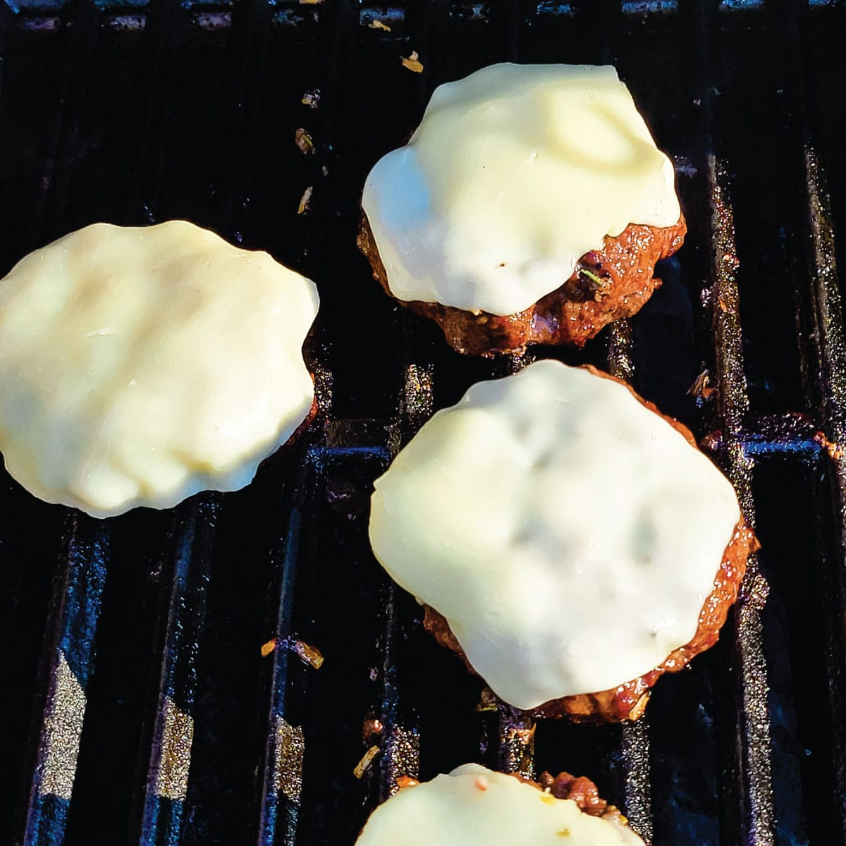 Burgers on the grill with cheese melting on them