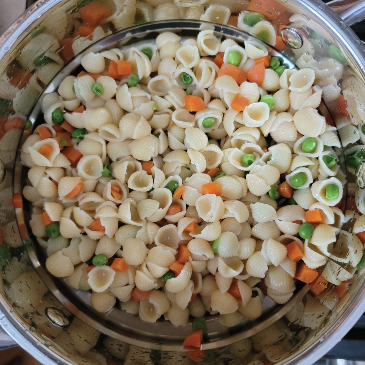 small shells, peas and carrots together in a strainer after being cooked and drained.