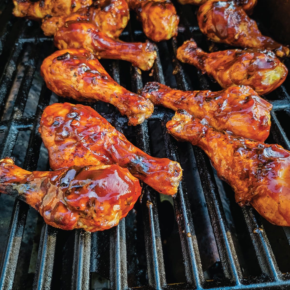 Chicken legs on the grill with BBQ sauce just added to them.