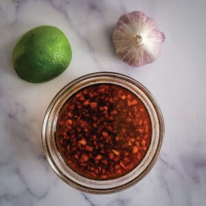 Marinade prepared and sitting in a bowl with a lime and head of garlic as decoration next to it