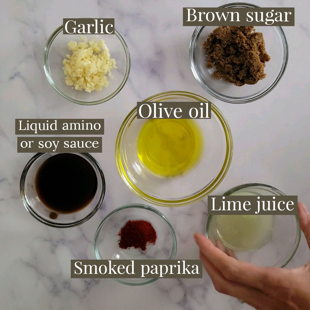 Ingredients for marinade in small prep bowls - garlic, brown sugar, liquid amino, olive oil, smoked paprika and lime juice