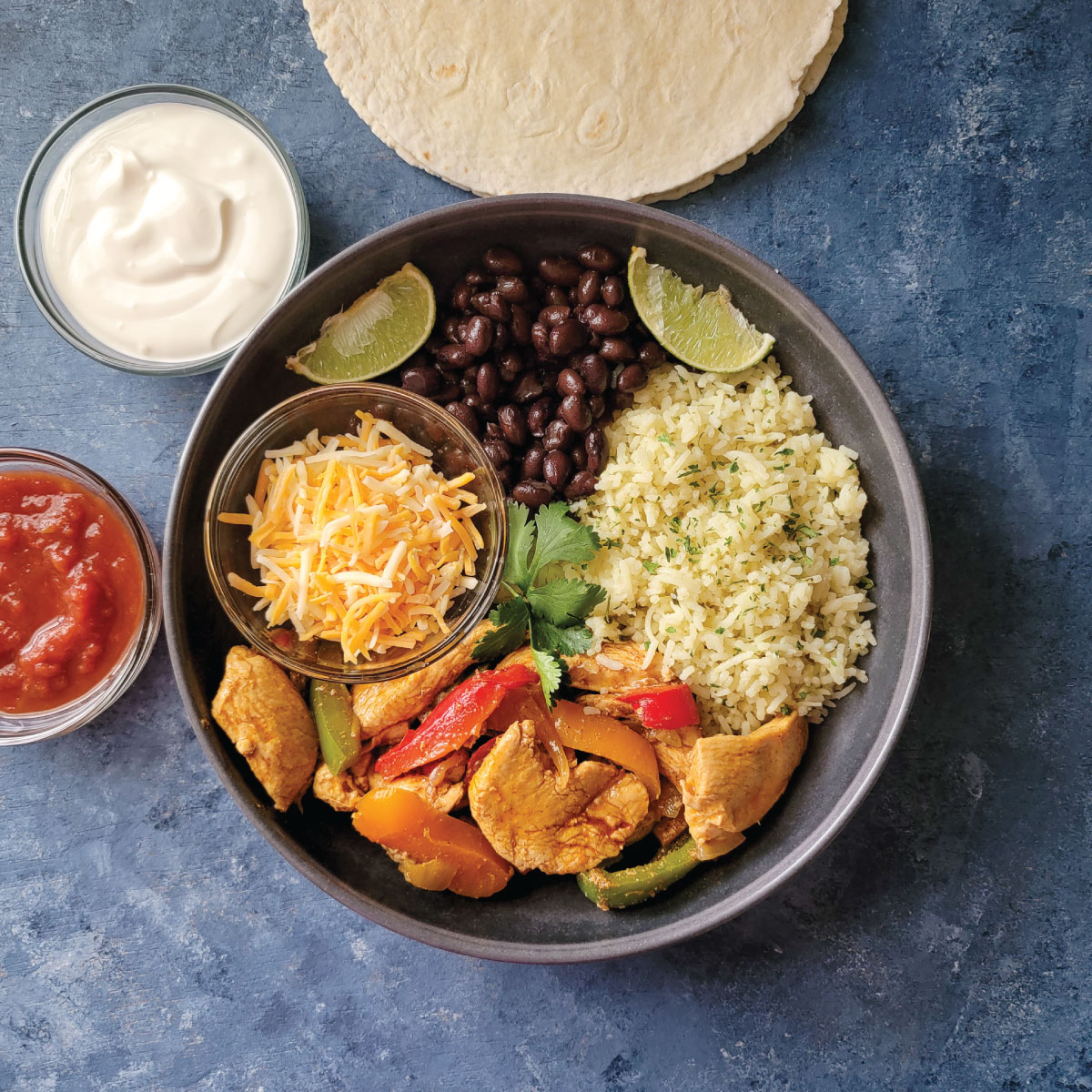 A dinner bowl with chicken fajita filling, rice, beans and cheese. Salsa and sour cream in side dishes.