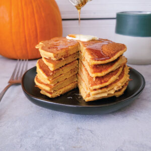 Stack of pumpkin pancakes on a plate with butter on top and maple syrup pouring over the top.
