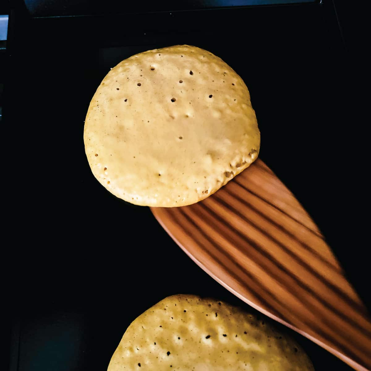 Batter on the griddle with a few bubbles forming in them as they are about to be flipped for the first time.