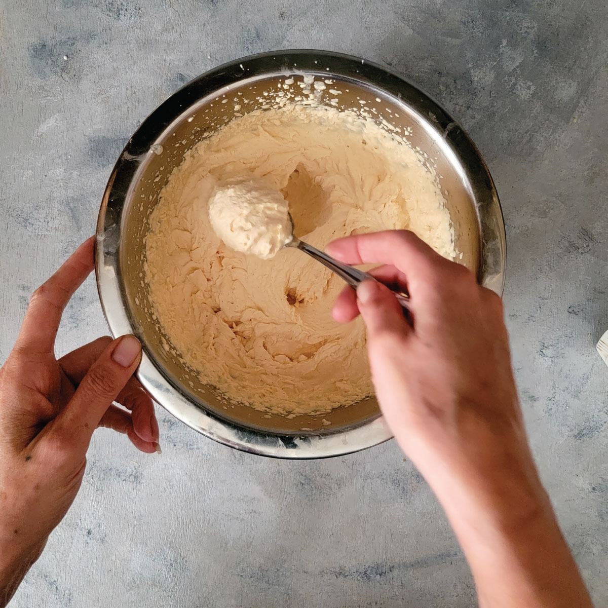 Whipped cream in a bowl with a spoonful scooped out to show the consistency of soft peaks.