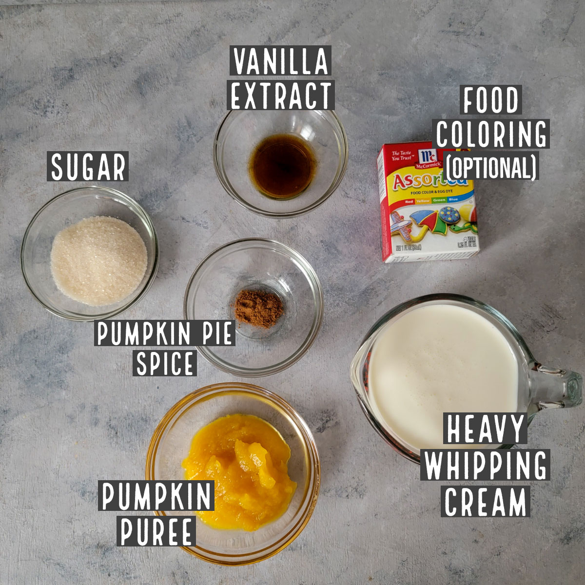 Pumpkin whipped cream ingredients in prep bowls - sugar, vanilla extract, food coloring (optional), pumpkin pie spice, pumpkin puree and heavy whipping cream.