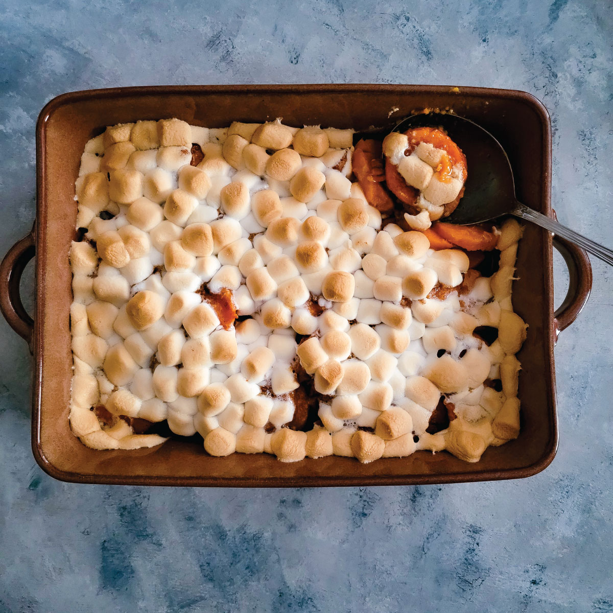 Sweet potato casserole in the baking dish after baking with a golden marshmallow top.