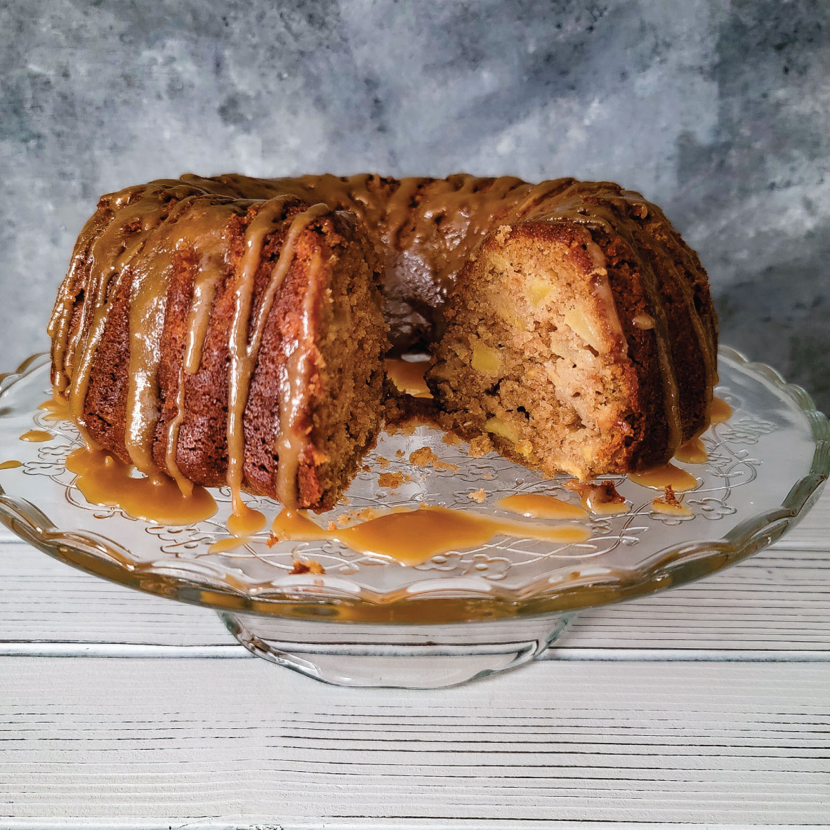Apple cake with caramel drizzled over the top on a cake platter with a piece of cake cut out to show the apples on the inside.