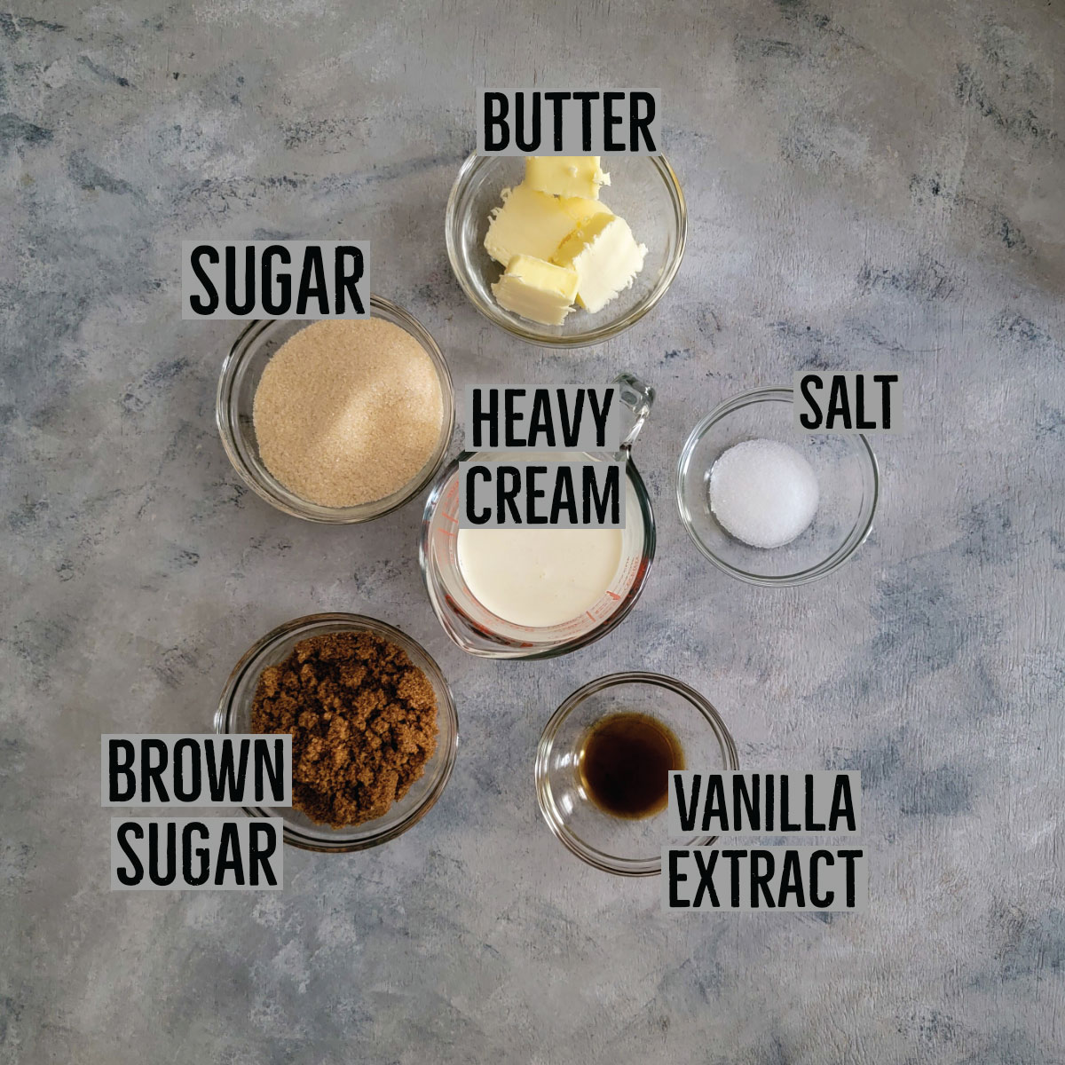 Ingredients for salted caramel in prep bowls - butter, salt, vanilla extract, brown sugar, sugar and heavy cream.